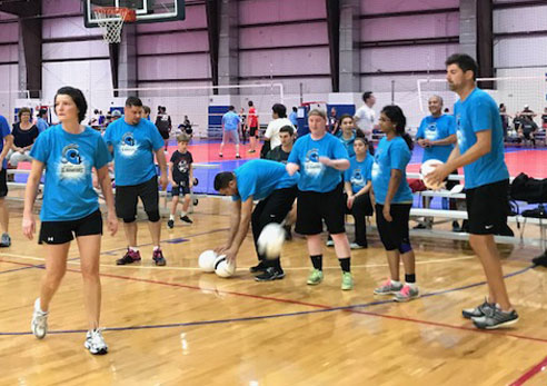 Employees playing volleyball during Corporate Challenge